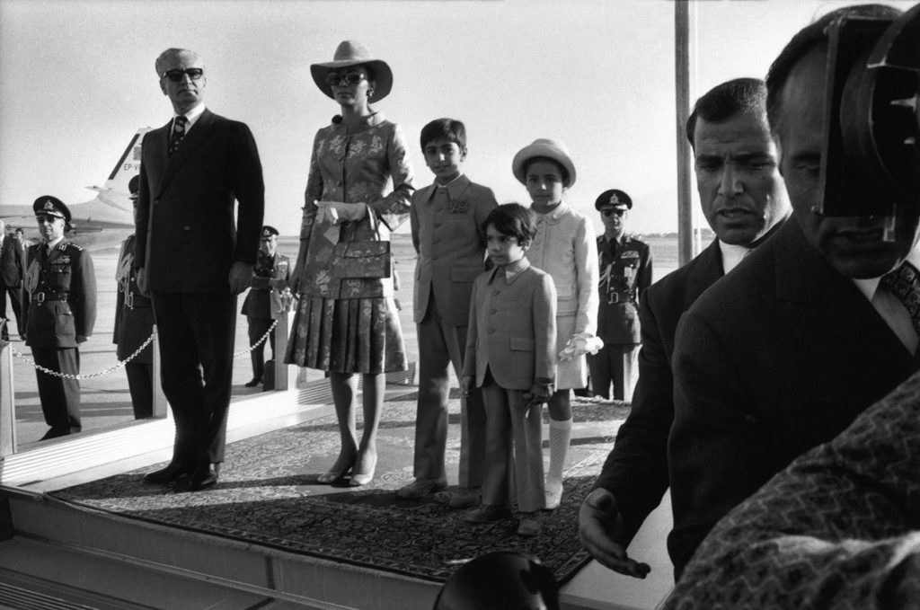 Shah Mohammad Reza PAHLAVI, Queen FARAH, Crown Prince REZA, Prince ALI and Princess FARAHNAZ take the stand upon arrival at the airport to celebrate the 2500th anniversary of the monarchy in Persepolis.