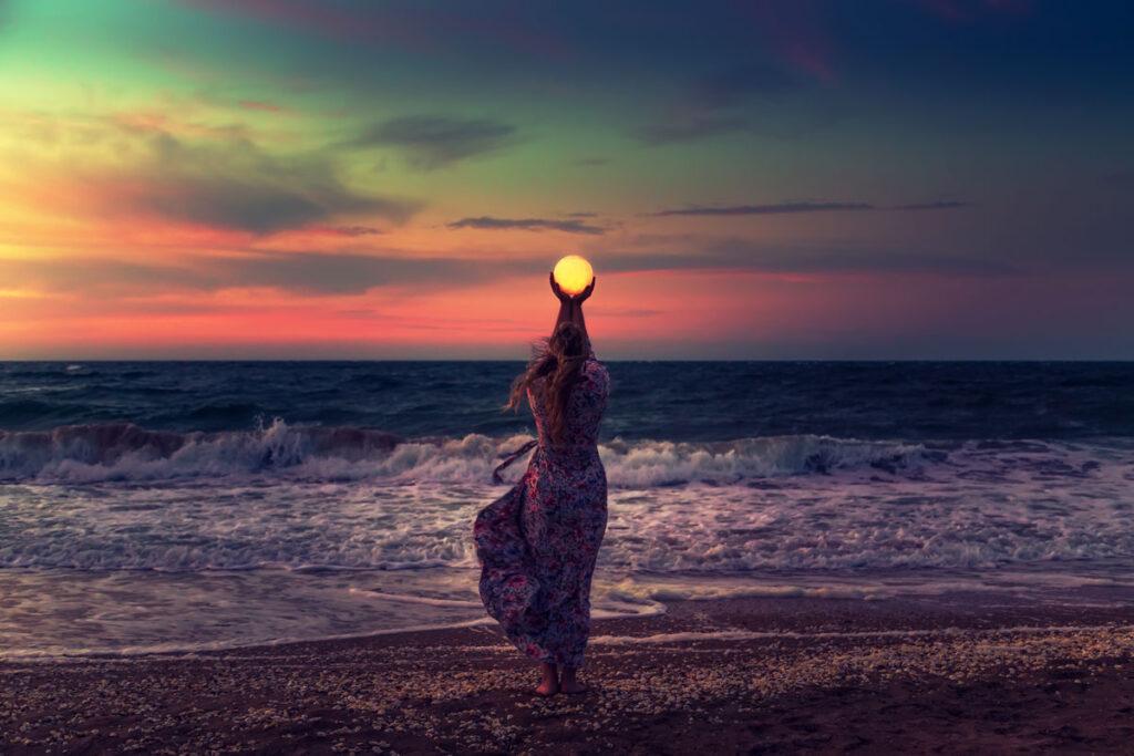 فتاة تحمل القمر بين يديها عند غروب الشمس الجميل على البحر